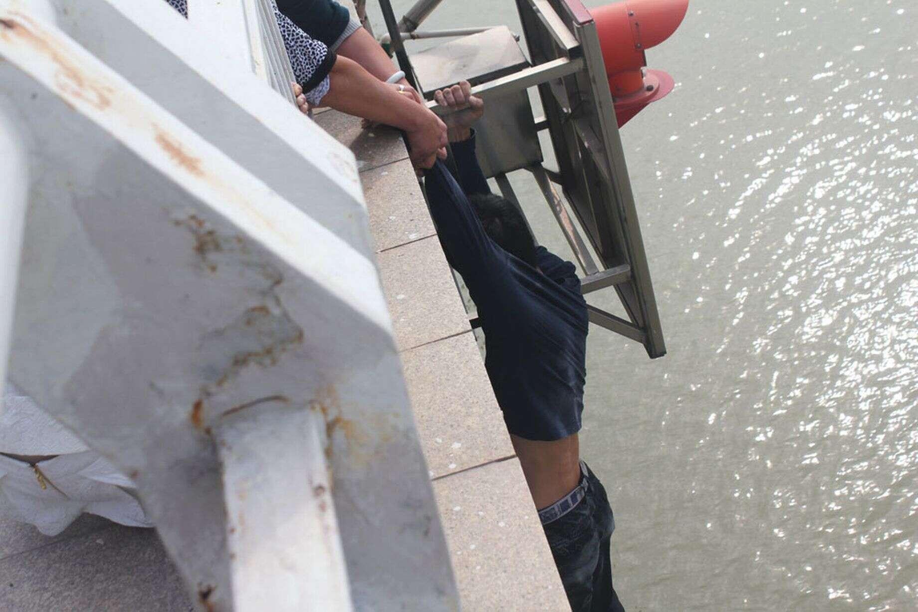 Mãe segura braço do filho após jovem saltar de ponte em tentativa de suicídio