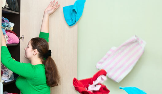 Mulher tirando peças do guarda-roupas