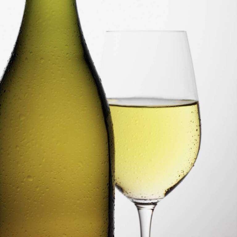 Bottle of white wine beside glass of white wine indoors