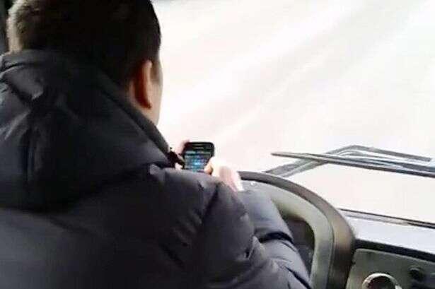 Motorista joga no celular enquanto dirige com os cotovelos
