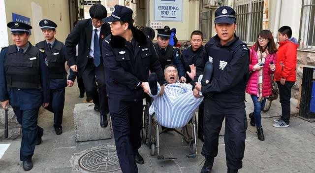 Homem é retirado à força pela polícia em cama de hospital