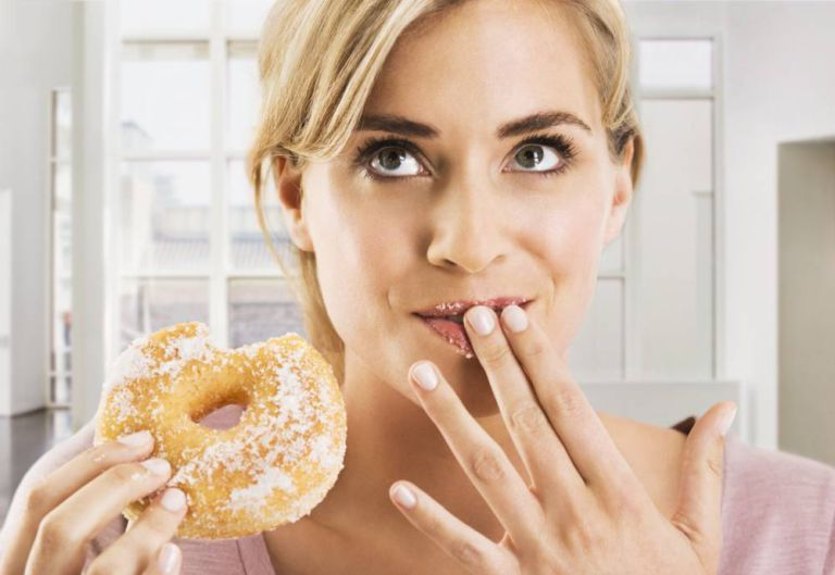 Blonde woman eating a sugar coated doughnut