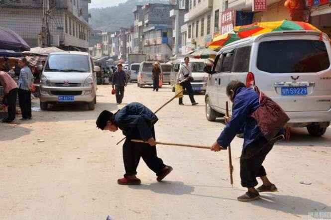Casados há 55 anos, mulher corcunda guia marido cego todos os dias usando bambu