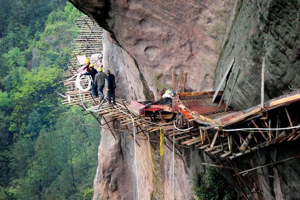 Funcionários arriscam suas vidas para construir passarela em penhasco