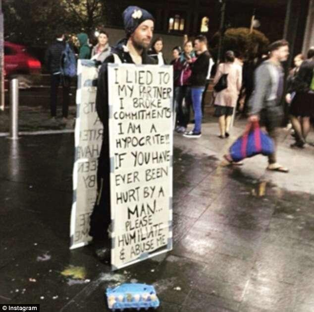 Homem permite que pessoas atirem ovos nele enquanto se veste com cartaz onde assume que traiu sua companheira