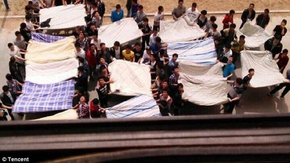 Estudante chinesa ameaça se jogar do 13º andar de prédio e grupo de ciclistas rapidamente usa lençóis para evitar que ela se ferisse