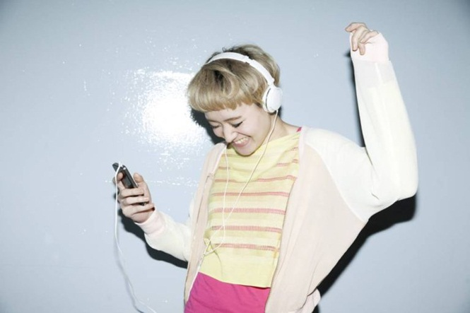 Japanese woman dancing with music on smartphone