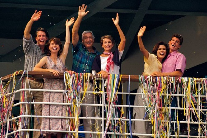 Couples waving from deck of cruise ship
