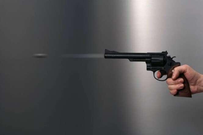 Hand holds discharging gun.