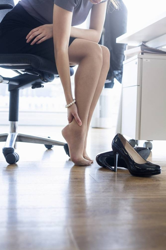 Neck down view of businesswoman massaging ankle at office desk