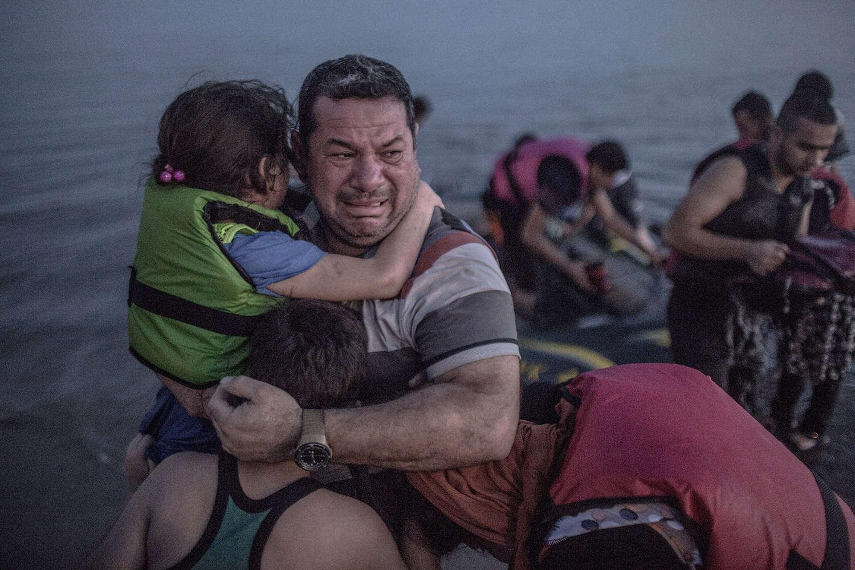 Foto surpreendente de pai abraçando seus filhos ao escapar da guerra na Síria comove o mundo