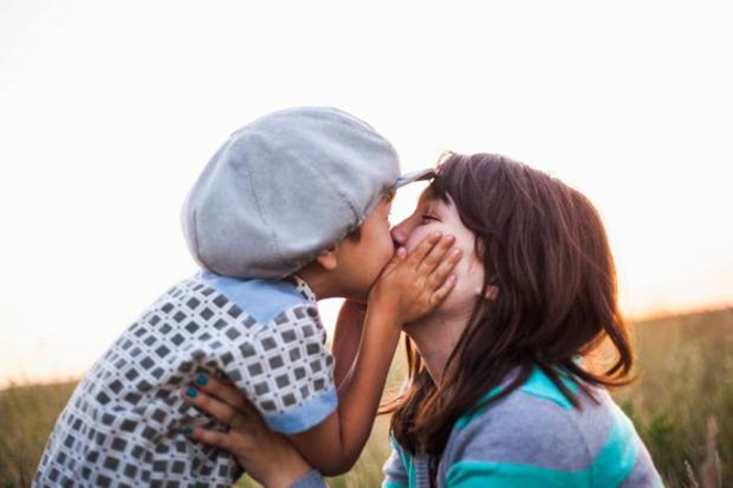 EXF8YY Close up of boy kissing mother in field