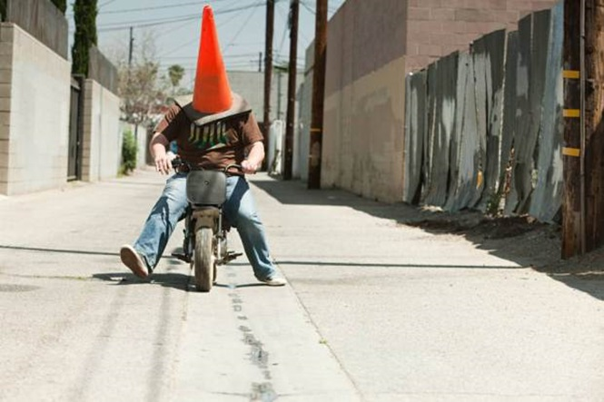 C6525H Man with traffic cone on head, riding motorbike