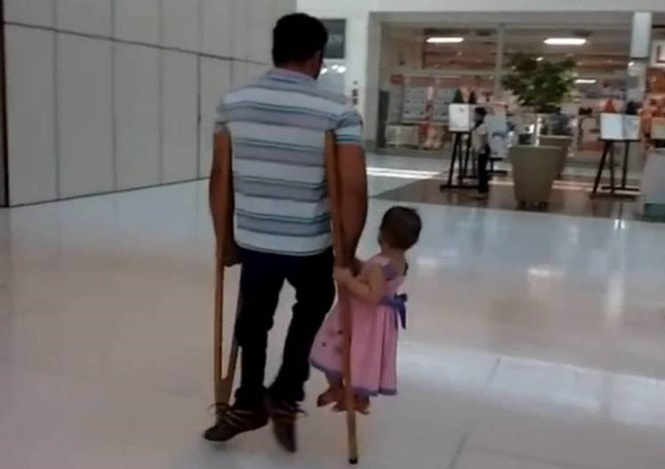 Pai com deficiência comove o mundo ao ser flagrado carregando filha pequena em suas muletas