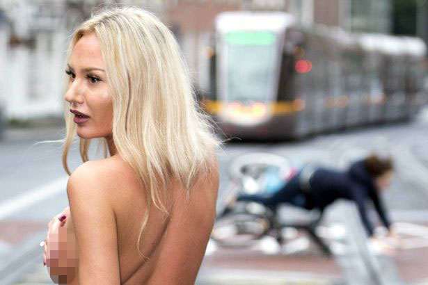 Ciclista leva tombo feio ao se distrair com modelo sem sutiã durante sessão de fotos
