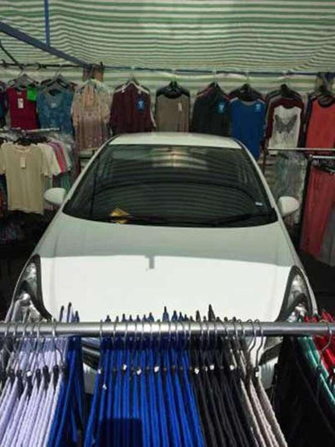 Vendedor monta barraca de roupas em torno de carro estacionado em local de feira
