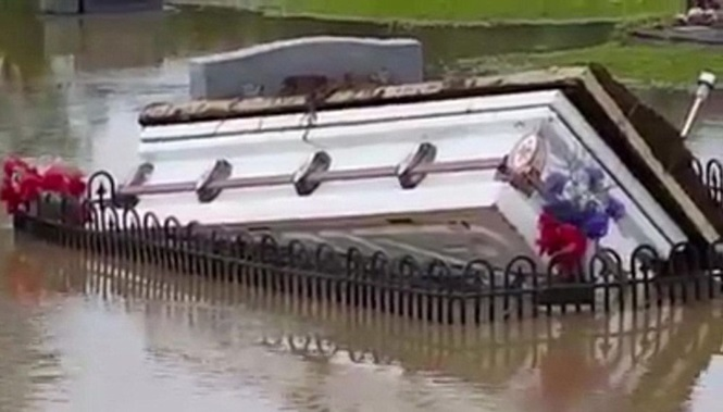 Caixões flutuam sobre as águas de enchente que atingiu cemitério nos EUA