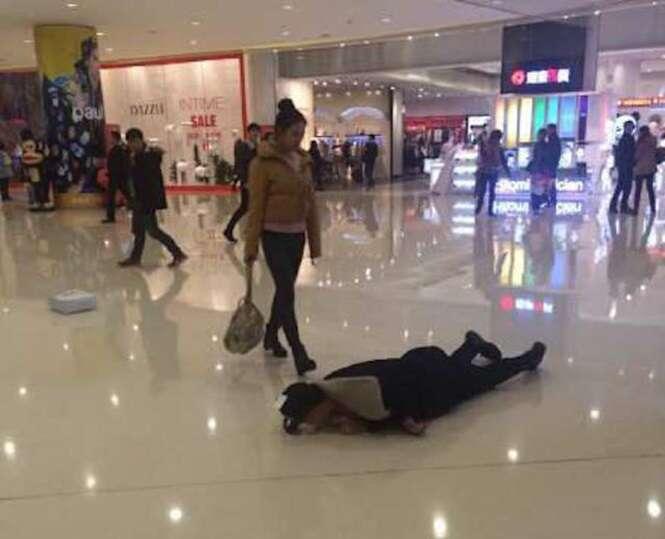 Jovem rola no chão à pedidos da namorado como forma punição por casal discutir em shopping