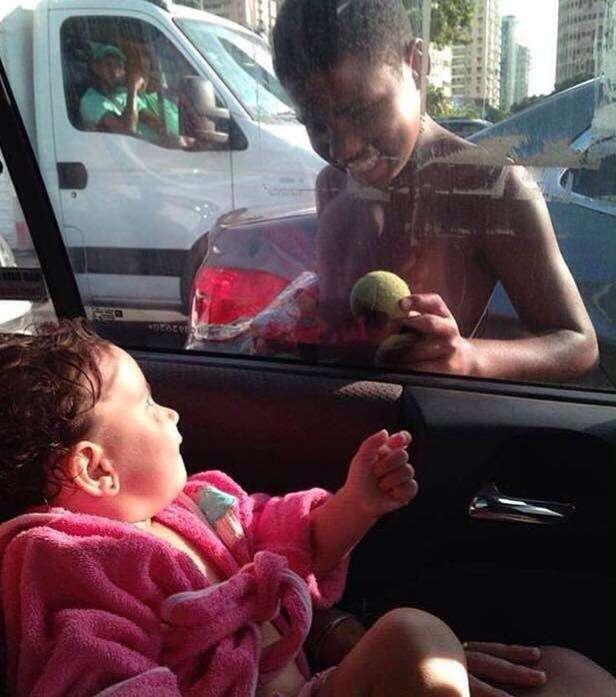 Menino de rua ganha nova esperança após ser fotografado brincando com bebê através da janela de táxi
