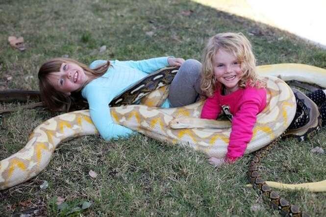 Pai causa polêmica ao permitir que seus três filhos brinquem com cobra píton de quase 6 metros
