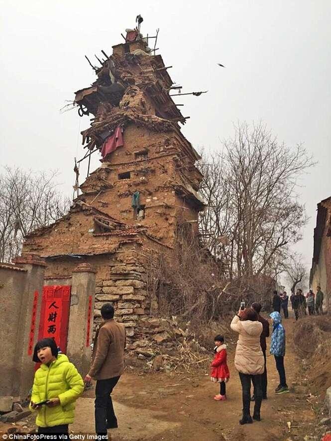 Homem constrói prédio de sete andares com argila e blocos de pedra à espera de irmãos mortos
