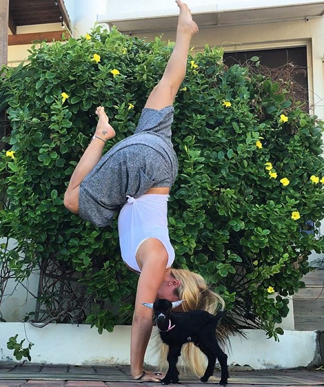 Garota exibindo movimentos de ioga junto de sua cabra de estimação