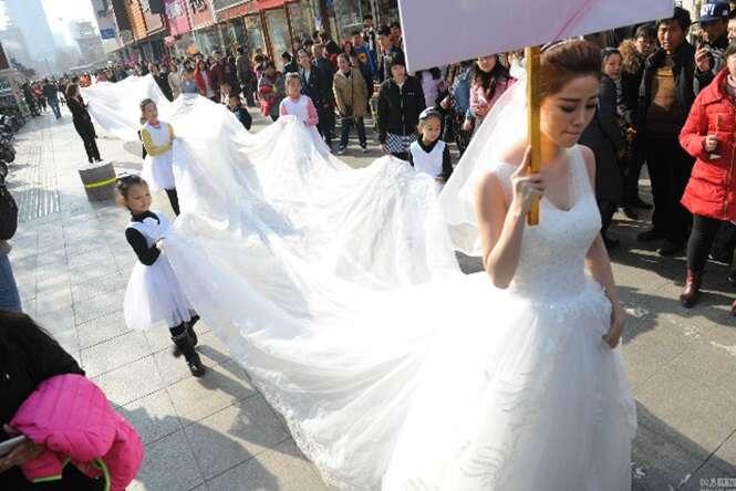 Modelo chama atenção ao caminhar com vestido de noiva de 101 metros de comprimento