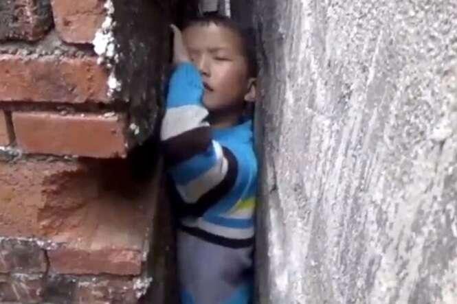 Bombeiros tentam retirar menino preso entre duas paredes