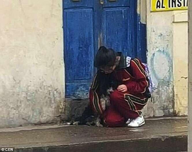 Menina é flagrada protegendo cão de rua da chuva e imagem comove internautas