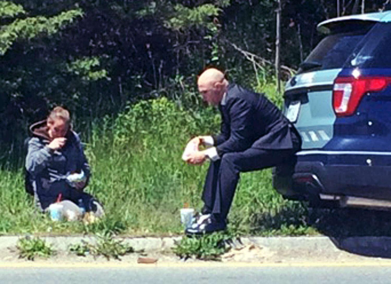 Policial norte-americano é flagrado comendo ao lado de moradora de rua