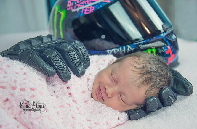 Bebê recém-nascido é embalado com luvas e capacete de pai falecido