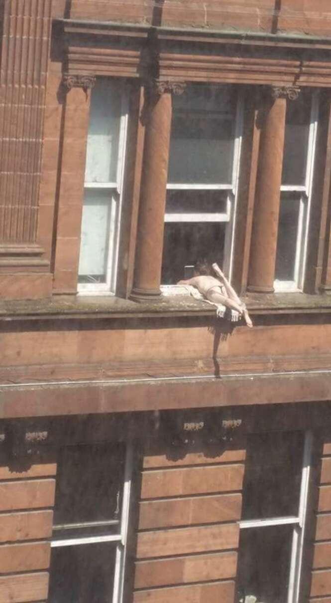 Mulher é flagrada se bronzeando deitada no parapeito de janela no terceiro andar de edifício