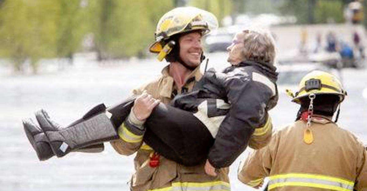 Bombeiro pega idosa nos braços durante resgate